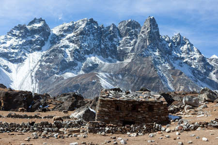 Shepherd's house in himalayas. Yaks pastures at high altitude in Nepal. Beautiful snowy mountains on the way to Renjo Pass in Everest region. Imagens