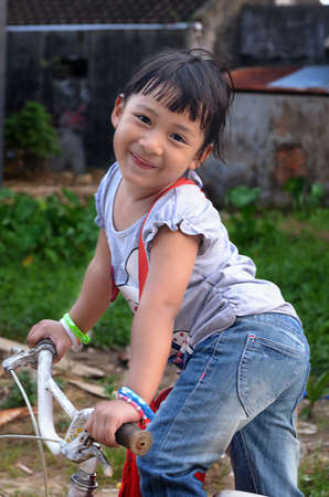 a little girl ride bicycle give her smile photo