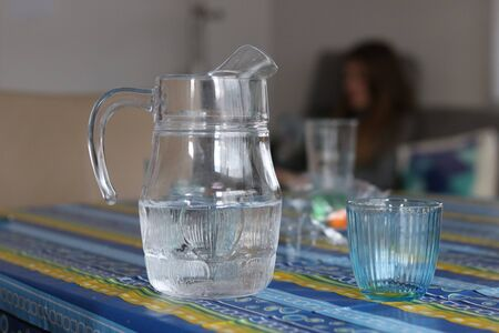 Glass Pitcher full and Blue Glass of Water