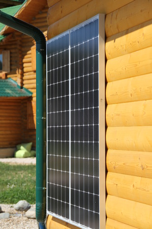 Solar battery on the yellow wall of a wooden house photo