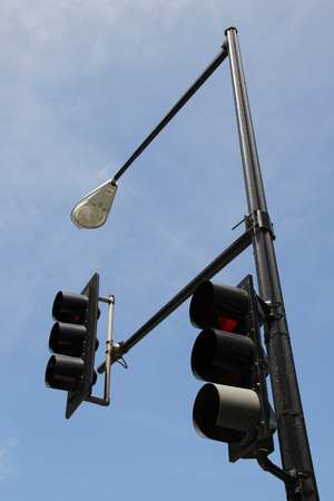 Two traffic light pole street lighting on the background of blue sky photo