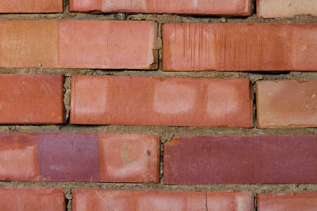 Background, a wall made of red bricks, partially crumbled. Bricks of different colours photo