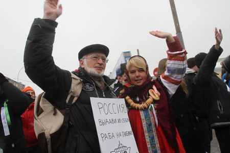 Moscow, Russia - February 26, 2012. environmentalists Andrey Margulev and Evgeniya Chirikova shares White ring in the protection of fair elections. The action occurred on the Russian holiday of Maslenitsa Evgenia Chirikova in traditional folk costume