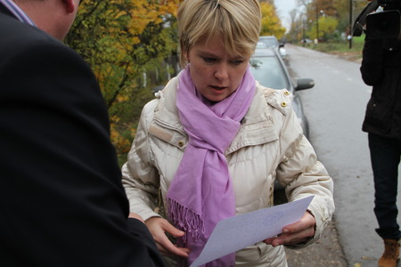 observer: Khimki, Moscow region, Russia - October 14, 2012. Candidate for mayor of Khimki opposition leader Yevgeniya Chirikova reads the complaint of an observer observing a policy violation on elections. On election day in the suburban town of Khimki broke sharp