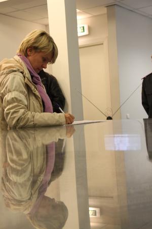 encuestando: Khimki, regi�n de Mosc�, Rusia - 14 de octubre de 2012. El candidato a la alcald�a de Khimki oposici�n Evgeniya Chirikova escribe una queja sobre violaci�nes en uno de los centros de votaci�n. El d�a de las elecciones en la ciudad suburbana de Khimki rompi� la fuerte competencia betwee