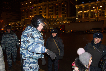 oppositional: Moscow, Russia - December 30, 2014. In day of a sentence to the oppositional leader Alexei Navalny and his brother Oleg Navalny Muscovites came to a protest action to Manezhnaya Square. The police officer sees off the child through a place of a protest ac