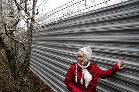 ecologist: Krasnodar region, Russia - March 23, 2012. The ecologist Evgenia Chirikova near a fence of a cottage of the governor Tkachyov in the protected wood