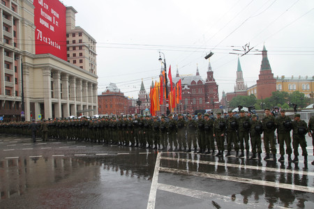 communists: Moscow, Russia - May 9, 2012. March of communists on the Victory Day. Cordon of police and the soldier of internal troops in front of the Kremlin during procession of communists