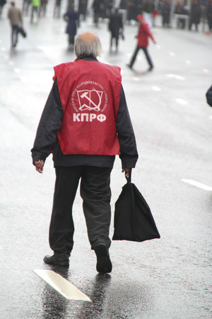 communists: Moscow, Russia - May 9, 2012. March of communists on the Victory Day. The lonely old man the pensioner with a bag in hands, in day of procession of communists