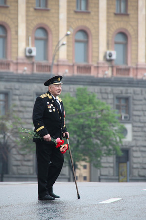 communists: Moscow, Russia - May 9, 2012. March of communists on the Victory Day. The unknown old man the veteran of war with awards, with flowers and in a uniform, in day of procession of communists