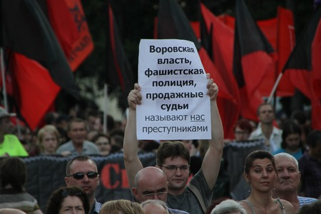 oppositional: Moscow, Russia - July 26, 2012. The person with the oppositional poster on meeting in protection of political prisoners. The first meeting in protection of the prisoners arrested for protest events on Bolotnaya Square on May 6, 2012 in Moscow Editorial