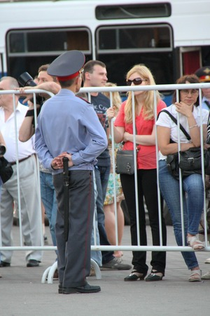 oppositional: Moscow, Russia - July 26, 2012. The police officer and the girl behind a fencing of oppositional meeting. The first meeting in protection of the prisoners arrested for protest events on Bolotnaya Square on May 6, 2012 in Moscow