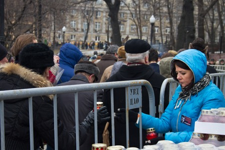 distribute: Moscow, Russia - March 3, 2015. The participants of the funeral of Boris Nemtsov distribute mourning candles. Farewell to the oppositionist Boris Nemtsov, who was killed near the Kremlin