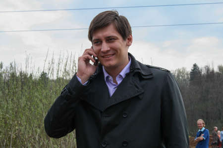 Politician Dmitry Gudkov speaks on the phone at the site of the deforestation of the Khimki forest Редакционное