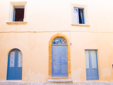 holliday: Otranto, Italy, Puglia, Old yellow facade with blue door and windows in old town center - Summer holliday Stock Photo