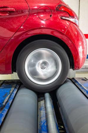 Bremstestleistung Hinterradantrieb in einem Autolabor mit dem Reifen, der auf den Rollen des Bremsprüfstands rollt