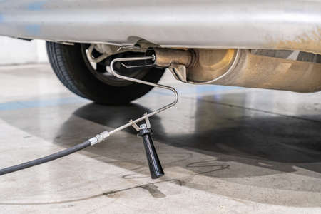 Emission control with a gas sensor in the exhaust of an old car at a vehicle inspection station