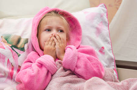 Little girl in bed in a warm bathrobe bewildered looks into the camera Stock Photo
