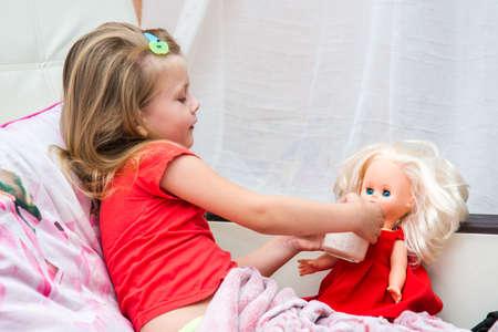 bathe mug: Little girl with a mug of milk watered doll Stock Photo