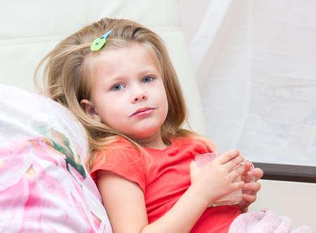bathe mug: Little girl with a mug of milk in bed