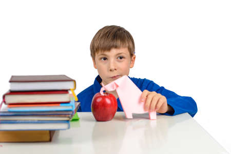 child development, origami: a schoolboy boy in a blue T-shirt sits at the table and plays with an elephant from paper, next to a stack of textbooks and a red apple