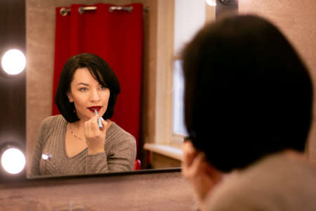 woman with black hair straightens makeup at the dressing table with a mirror