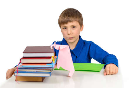 child development, origami: a schoolboy boy in a blue T-shirt sits at the table and plays with an elephant from paper, next to a stack of textbooks