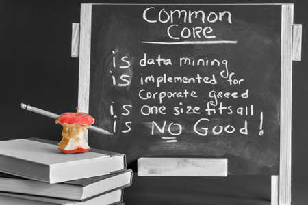 Common Core black board with books and eaten apple.
