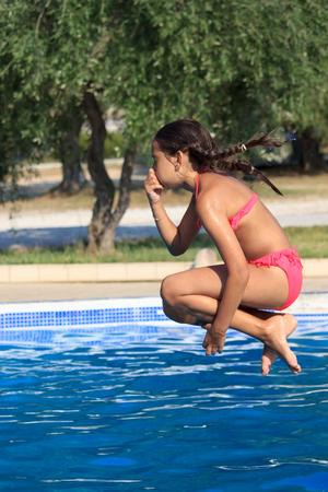 Girl jump in the pool photo