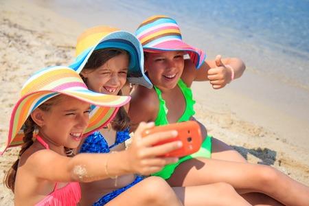 Girls making self portriat on the beach photo