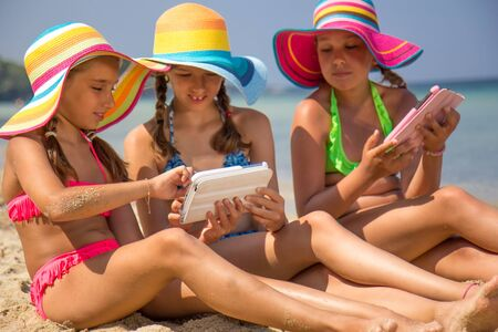 Girls with tablet on the beach photo