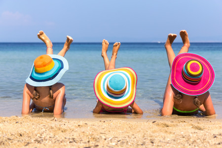 Girls with colorful hats on the beach Фото со стока