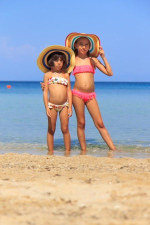 Girls with colorful hats on the beach Stock Photo