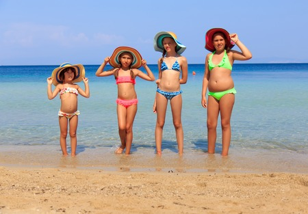 Girls with colorful hats on the beach Reklamní fotografie