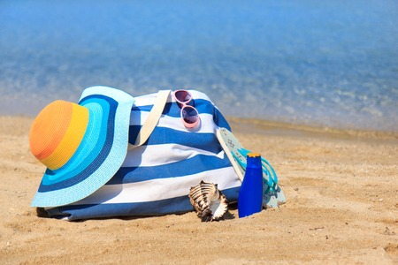 Colorful hat and bag on the beach photo