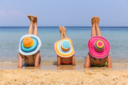 Girls with colorful hats on the beach Archivio Fotografico