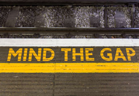 black and white railroad tracks: Mind the gap sign
