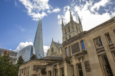 glass building: Southwark Cathedral and Shard building. South bank walk of the river Thames. Contrast of modern and old arhitecture.