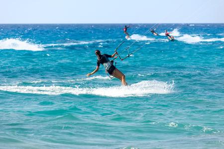 Een jonge vrouw kite-surfer rijdt in zomerdag