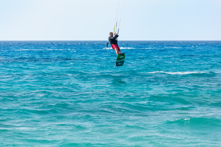 kiter: LEFKADA, GREECE - JULY 26, 2016: Unidentified man kite-surfer rides at famous Milos beach in summer day on July, 26, 2017 in Lefkada, Greece. Stock Photo