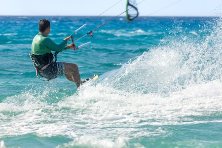 kiteboarding: Unidentified man kite-surfer rides at famous Milos beach in summer day in Lefkada, Greece.