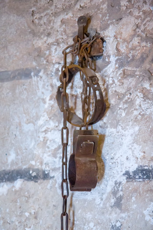 Old rusty shackles with chain on wall in prison