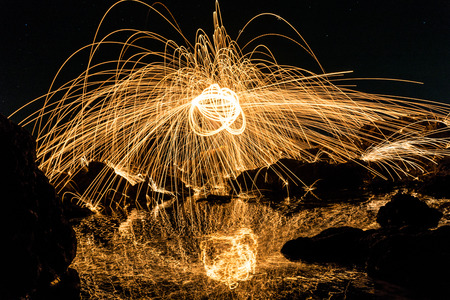 steel wool: A man playing steel wool on the beach at night