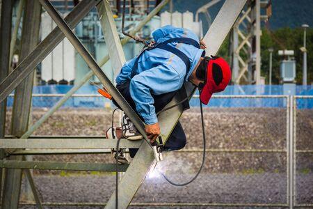 Welder work at high Electric high voltage pole 230 Kv