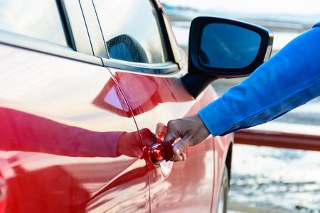 Close up of women hand opening door of car