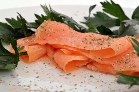 salmon ahumado: Closeup de salmón ahumado en un plato, decorado con hierbas y lechuga verde