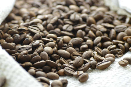 Roasted coffee beans over rustic background. Shallow dof. photo