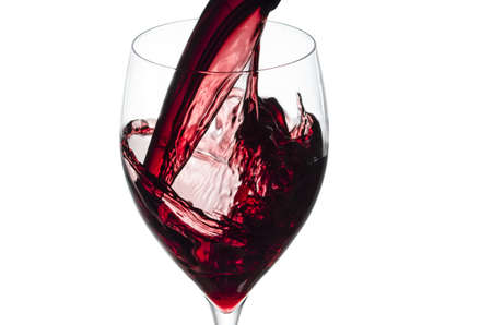 Glass of red wine splashing while being poured Isolated on white  photo