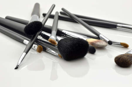 beauty make up: A bunch of make-up brushes lying randomly on white background with reflection