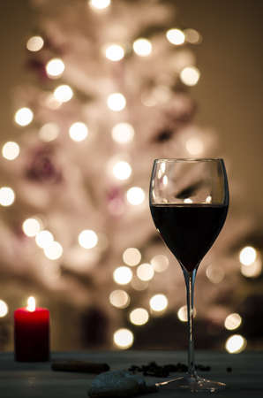 christmas drink: Wine glass on a table decorated with candle and cookies  Defocused lights on a white Christmas tree in background
